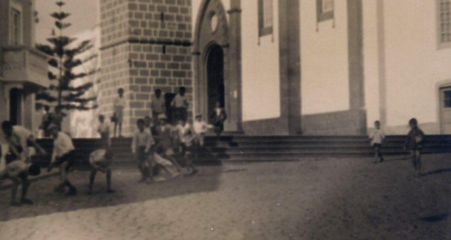 Detalle de la imagen antigua de niños y niñas jugando cerca de la iglesia de Santa Brígida